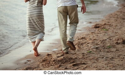 young lovers walking on the sandy shore of the lake at sunset