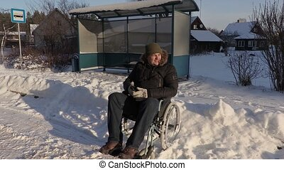 Disabled worker on wheelchair expects bus