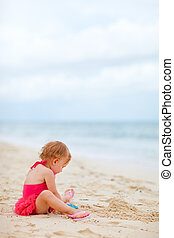Toddler girl playing with toys at beach