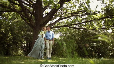 Young, stylish, beautiful pair of newlyweds walking in the park