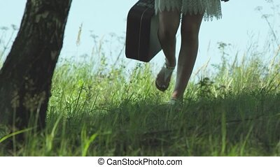 Girl with a suitcase running on the green grass in wild nature.
