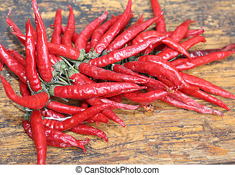 red hot peppers on wooden table at market - red hot peppers...