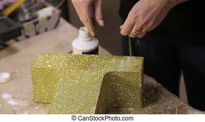Golden glitters on wooden brick letter