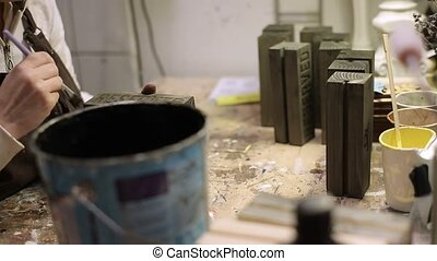 Woman paints wooden brick in gray color