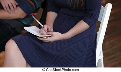 Woman writing in notebook on lecture