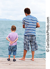 Father and son fishing from pier