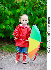 Toddler girl with umbrella outdoors on rainy autumn day -...