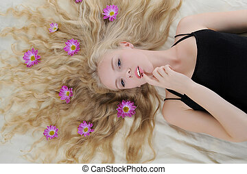 Long-haired blonde with flowers in their hair