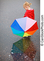 Toddler girl with colorful umbrella on rainy day - Toddler...
