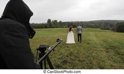Wedding couple in field backstage video shooting with camera...