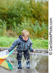 Boy jumping in puddle - Playful boy jumping in puddle on...