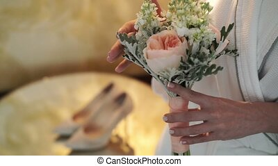 Young woman in bathrobe staying with bouquet, shoes on...