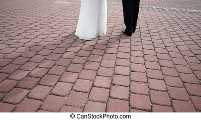 Bride and groom walks in the city at cloudy day