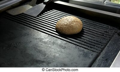 Burger sesame buns. Hand putting bread on pan. Soft and...