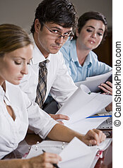 Businessman reviewing documents with female colleagues