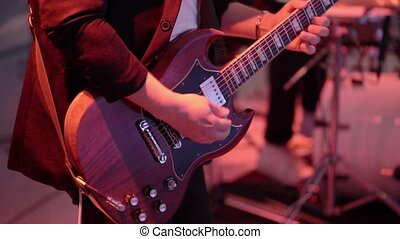 Man playing guitar on concert closeup