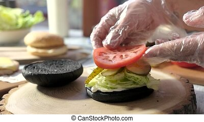 Hands making cheeseburger. Vegetables and patty with cheese....