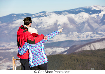 Rear view of a loving couple in fur hood jackets looking at...