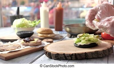 Hands preparing cheeseburger. Wood board and burger. Fast...