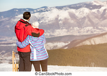 Rear view of a loving couple in fur hood jackets looking at snowed mountain range