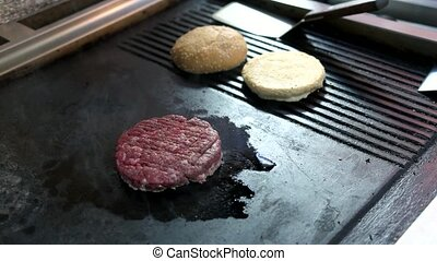 Raw burger patty. Male hand with pepper mill. Quality beef...