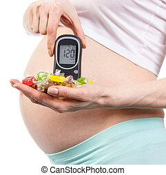 Pregnant woman with glucometer and colorful candies, diabetes and healthy nutrition during pregnancy