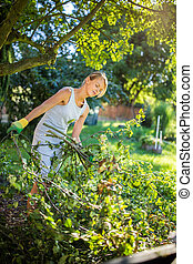 Pretty, young woman gardening in her garden, cutting branches