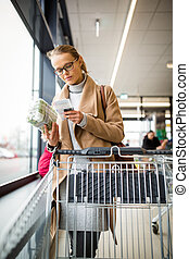 Pretty young woman buying groceries in a supermarket/mall/grocery store - checking the bill after paying with a credit card for her purchase