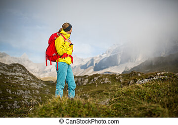 Pretty, young female hiker walking in high mountains...