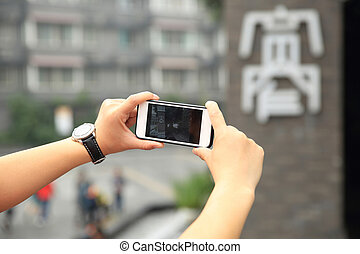 young woman tourist taking photo with cellphone on street in...