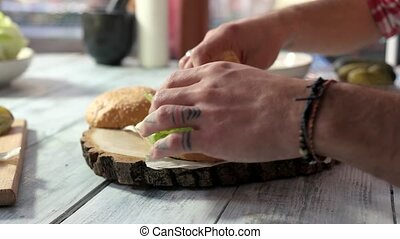 Closeup of hands making cheeseburger. Sliced vegetables,...