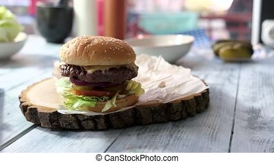 Burger on wooden board. Hamburger on gray table. Eat daily...