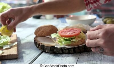 Hands making sandwich with vegetables. Tomato, sliced pickle...