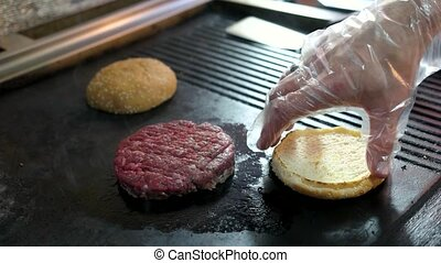 Raw patty on pan. Hand and sliced buns. Ingredients of beef...