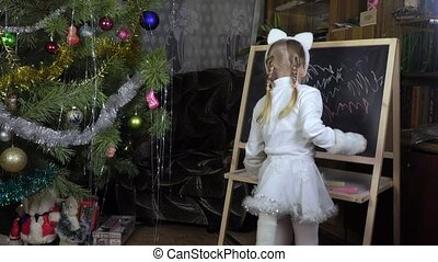 Little girl draws chalk on blackboard - On blackboard little...