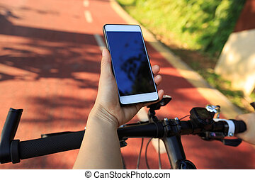 cyclist setting active camera before riding mountain bike on...