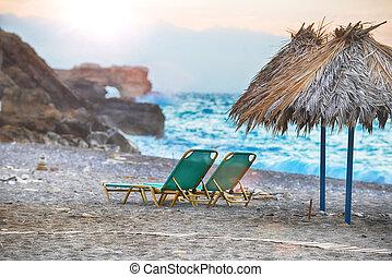 sea beach - Beach chairs with straw umbrellas on sea beach