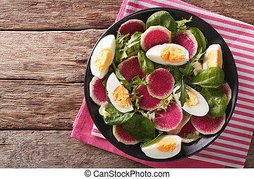 Tasty salad of watermelon radishes, eggs, spinach and herbs...