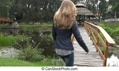 woman walk to wooden arbor on bridge through sink river in park.