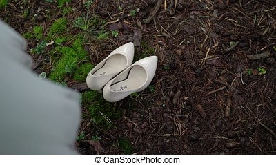 White shoes on grass in forest and wedding dress on a tree