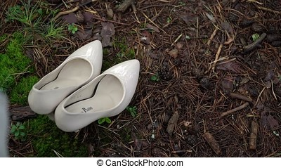 White shoes on grass in forest and wedding dress