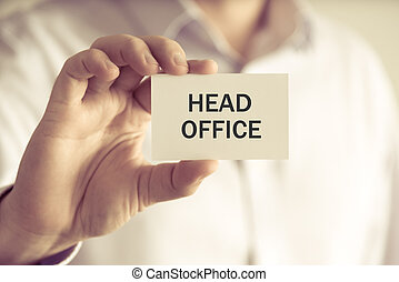 Businessman holding HEAD OFFICE message card - Closeup on...