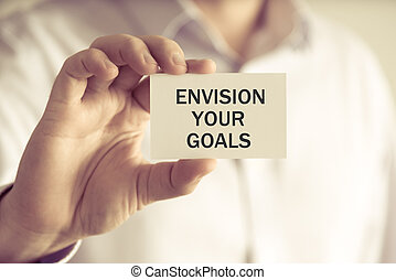 Businessman holding ENVISION YOUR GOALS message card -...