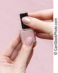 Beautiful female hand with warm pink nail design holding...