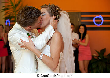 A passionate kiss between newlyweds standing in an orange...