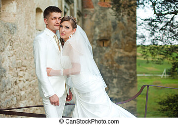 Beautiful bride looks thoughtful holding her hands on groom's waist