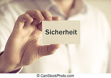 "Businessman holding message card ""SICHERHEIT"" written in..."