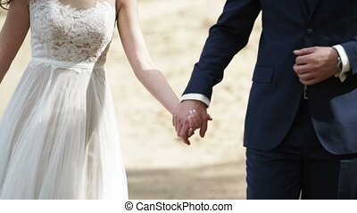 Wedding couple walks on a beach and holding hands