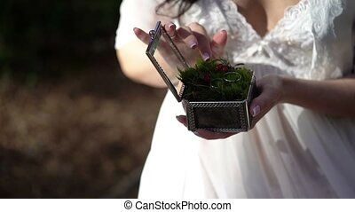 Young woman holding box with wedding rings at sunny day
