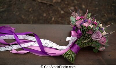 Bouquet with violet and white ribbons outdoors